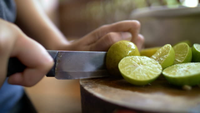 vídeos de stock e filmes b-roll de hands cutting lemon with knife on cutting board. - lima