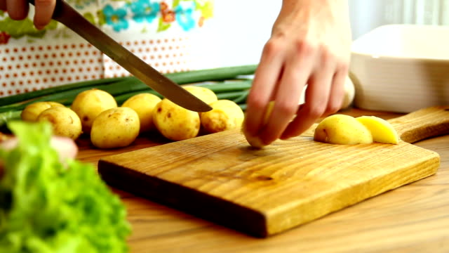 Hands cutting potatoes on wooden board. video