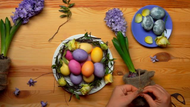 Hands decorate a hyacinth flower pot with burlap for the Easter composition video