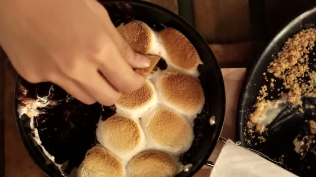 Hands dipping cracker in marshmallow chocolate heated in pan, Smore video