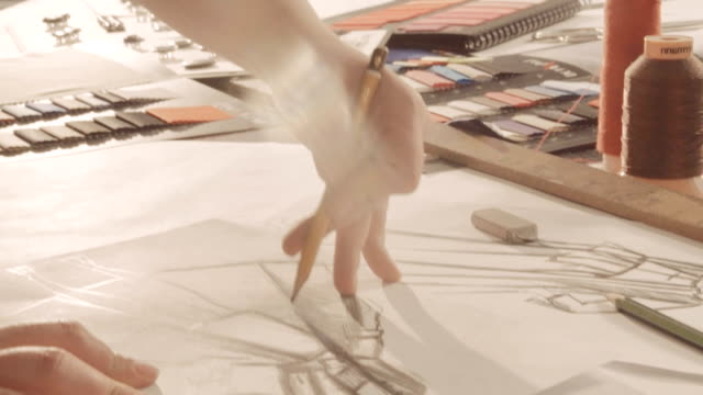 Hands draw with a pencil. Designer draws a line on the paper. Close-up video