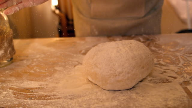 Hands dropping ball of dough onto floury surface video
