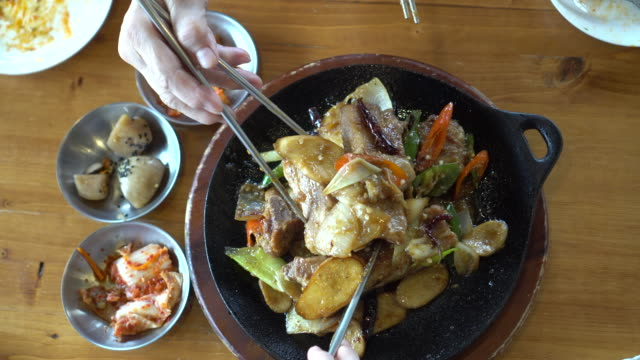 hands eating korean pork ribs on hot pan together - cultura coreana video stock e b–roll