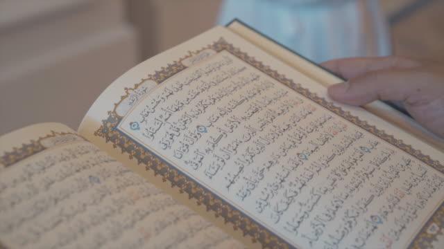 stockvideo's en b-roll-footage met flipping pagina's van oude arabische boek handen - koran