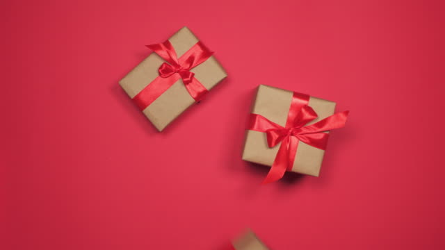 Hands grabbing gift boxes on red flat lay Top view of hands grabbing group of gift boxes on red flat lay gifts stock videos & royalty-free footage