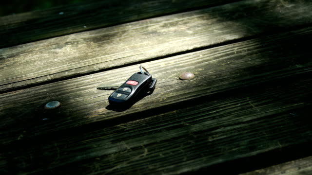 hands grabbing keys on wooden table - chiave video stock e b–roll