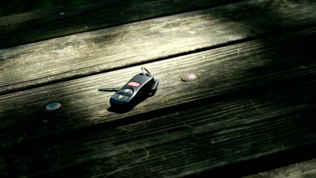 hands grabbing keys on wooden table - avvicinarsi video stock e b–roll