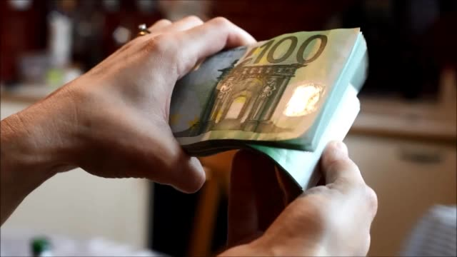 hands handling a wad of hundred-euro bills.