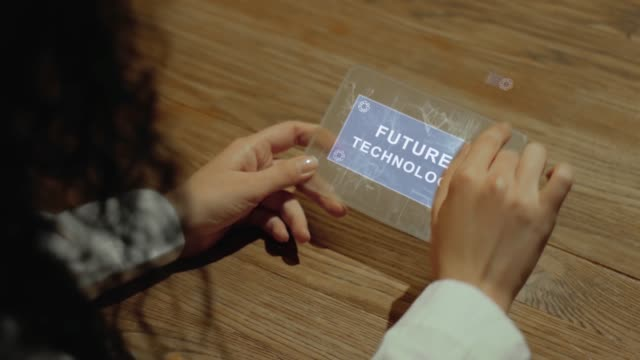 Hands hold tablet with text Future technology Unrecognizable woman working on a futuristic tablet with a hologram text Future technology. Women's hands with future holographic technology at a wooden table multimedia stock videos & royalty-free footage