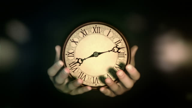 Hands holding a clock. Cinematic color grading. video