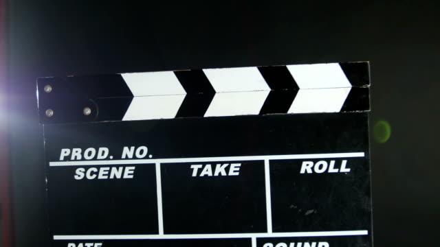 vidéos et rushes de mains tenant un film clapper conseil, sur noir, gros plan, lumière dos - ardoise