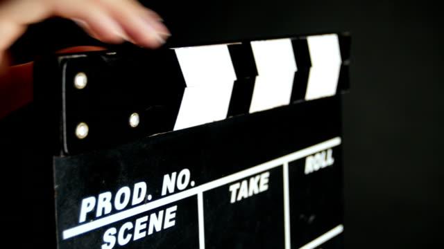 vidéos et rushes de mains tenant un film clapper conseil, sur noir, gros plan - ardoise