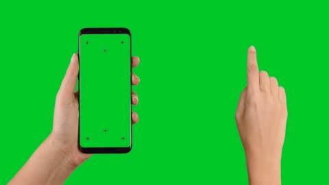 vídeos de stock, filmes e b-roll de mãos segurando um telefone inteligente e tocando em deslizamento - smartphone