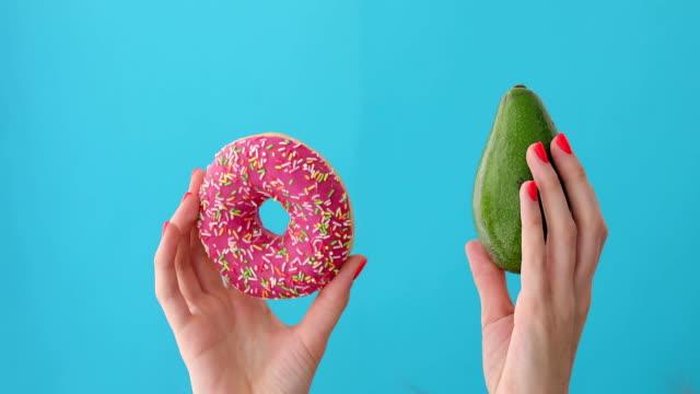händer som håller avokado och munk - fett näringsämne bildbanksvideor och videomaterial från bakom kulisserna