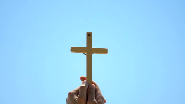 vídeos de stock e filmes b-roll de hands holding cross against sky background, christian baptism, spirituality - crucifixo