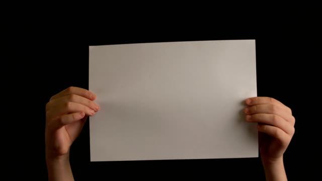 vídeos de stock e filmes b-roll de hand's holding crumpled paper on black background - amarrotado