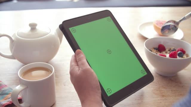 vidéos et rushes de mains tenant la tablette numérique avec écran vert sur le petit déjeuner - infusion pamplemousse