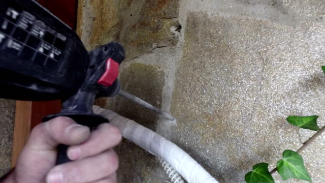 hands holding electric drill in room, interior design and home renovation DIY concept video