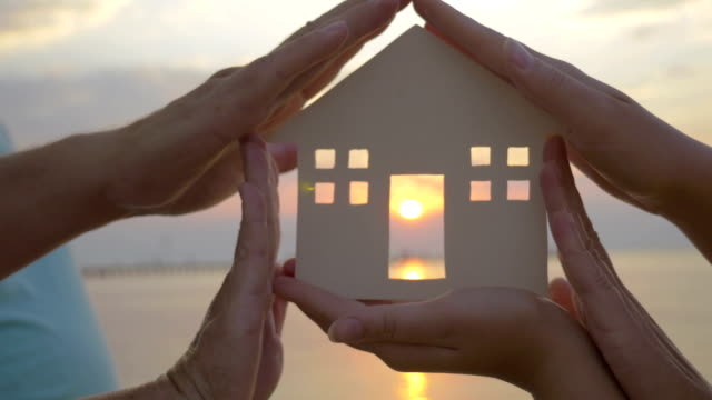 Hands Holding House Silhouette against Sun video
