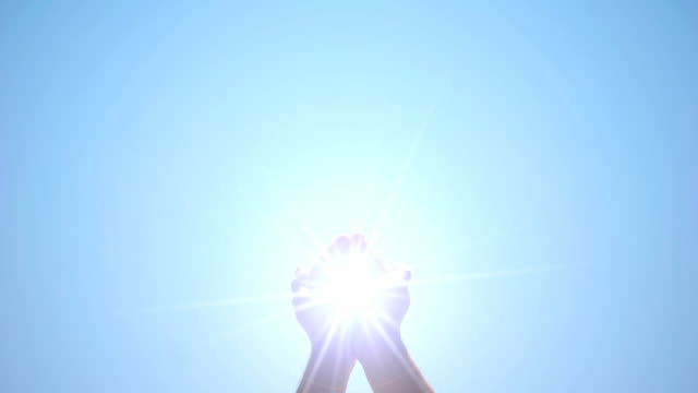 hands holding sacred light against blue sky, religious miracle, ray of hope - palm of hand stock videos & royalty-free footage