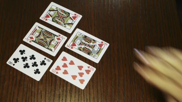 hands holding shuffle playing card deck on wooden table