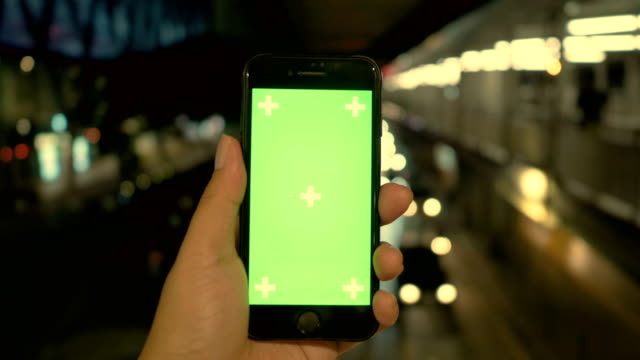 Hands holding smartphone with greenscreen display