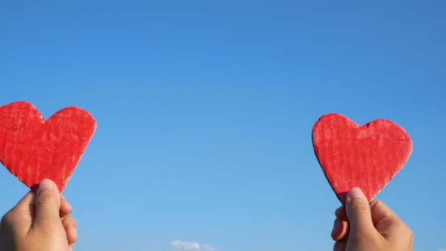händer som håller två röda hjärtformade återvunnen kartong på blå himmel bakgrund. kärlekssymbol för alla hjärtans dag. begrepp om kärlek och romantik. - recycling heart bildbanksvideor och videomaterial från bakom kulisserna