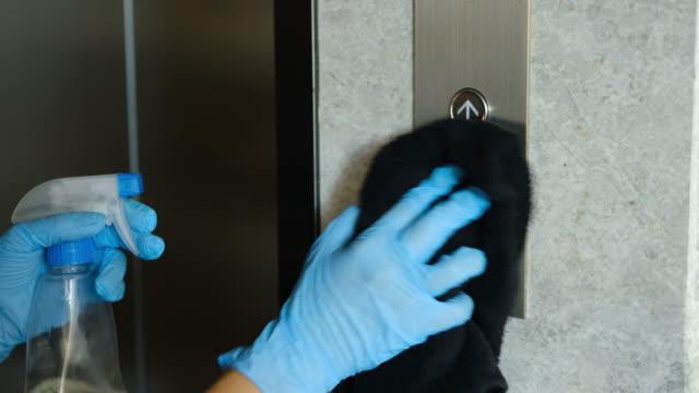 eller mavi lastik eldiven temizleme ve alkol dezenfekte sprey kullanarak asansör düğmeleri dezenfekte. antiseptik, dezenfeksiyon, temizlik ve sağlık bakımı. covid-19 salgınının enfeksiyon dan önlenmesi - coğrafi konum stok videoları ve detay görüntü çekimi