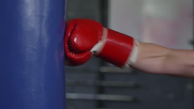 Hands in Boxing Gloves Punching Heavy Bag