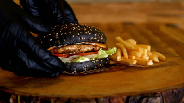 Hands in gloves put a juicy black burger with big cutlets and vegetables on the wooden board next to the French fries. Unhealthy fast food.