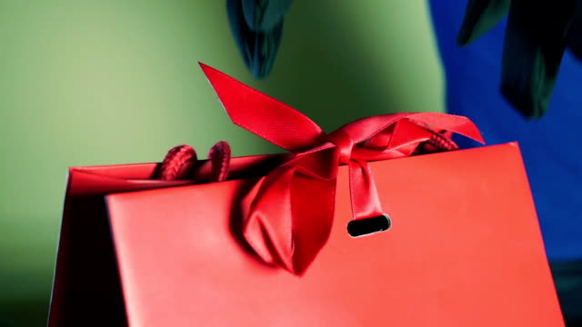 Hands in gloves untie a red ribbon of a luxury gift bag