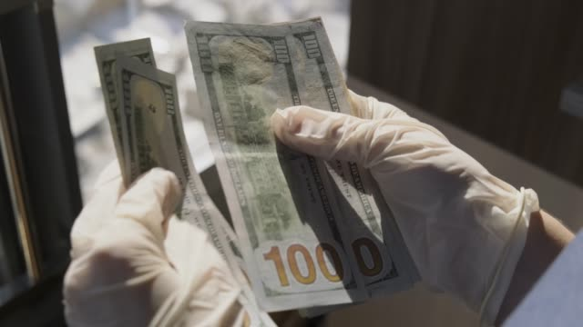 Hands in white gloves recount money, near window, through window you can see street, remaining money will be spent on credit and mortgages, how to survive in this world, economic crisis is brewing