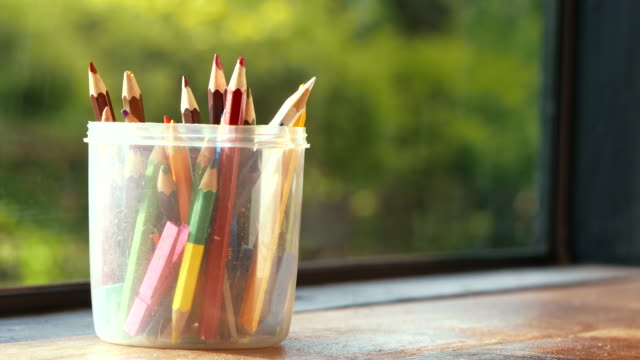 Hands keep colored pencils in a plastic round box placed on a wooden table by the window with the sun shining on green nature bokeh background.