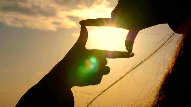 hands making a frame sign over sunset - rama obrazu filmów i materiałów b-roll