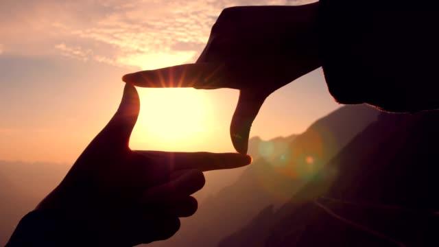 händer att göra en ram logga över sunset - ram bildbanksvideor och videomaterial från bakom kulisserna
