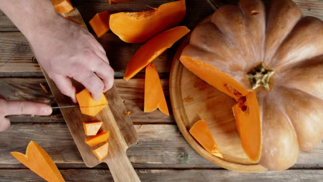 Hands men cut the pumpkin into pieces on a cutting Board.