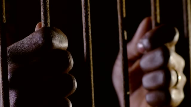 hands of a black man holding the prison bars.Jail, imprisonment, crimes video
