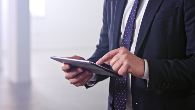 Hands of a businessman typing on a digital tablet he is holding video