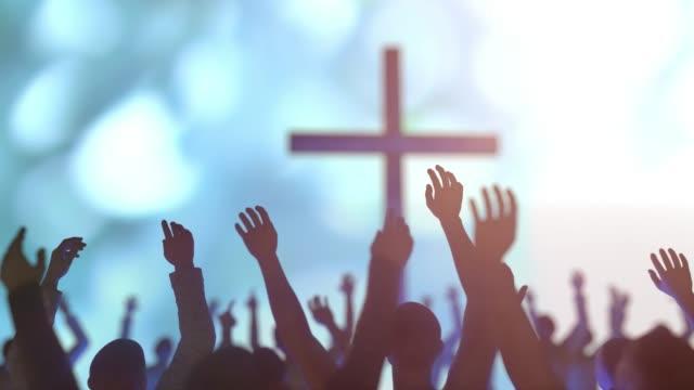 stockvideo's en b-roll-footage met handen van een menigte van mensen bij een christelijke vergadering tijdens de verheerlijkingsl van god tegen de achtergrond van het kruis 3d maken - kerk