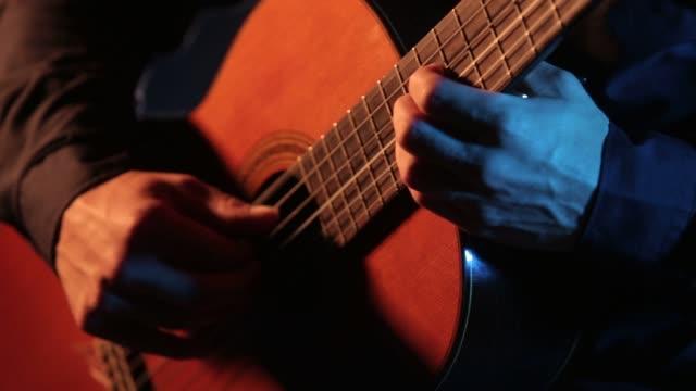 händerna på en gitarrist som spelar gitarr, närbild av strängar och hals - akustisk gitarr bildbanksvideor och videomaterial från bakom kulisserna