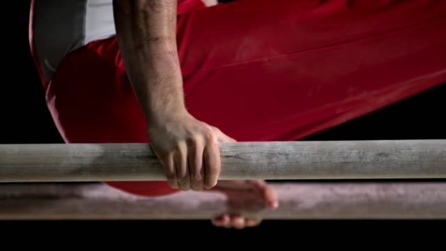 SLO MO Hands of a gymnast during his routine on parallel bars