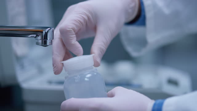 Hands of a laboratory technician taking a sample of water from the tap and writing on the bottle