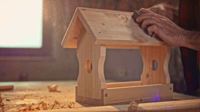 slo mo hands eines männlichen schreiners, der das vogelhaus in der sonnigen werkstatt schleifen - tischlerarbeit stock-videos und b-roll-filmmaterial