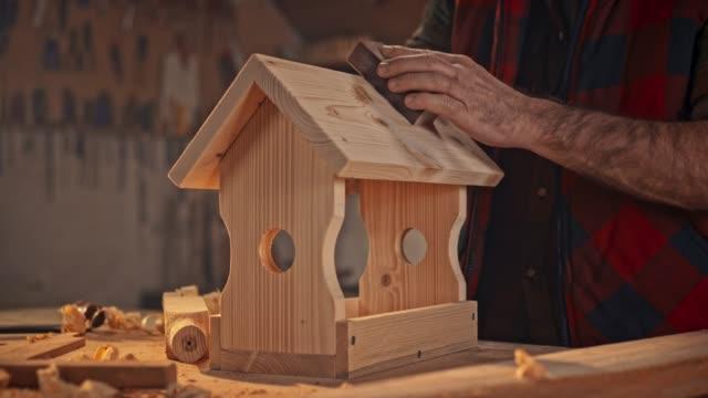 händerna på en manlig snickare efter behandling ytan av ett fågel hus med hjälp av en slipsvamp - aktivitet bildbanksvideor och videomaterial från bakom kulisserna