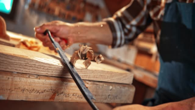 SLO MO DS Hands of a male carpenter holding a draw knife and trimming a plank
