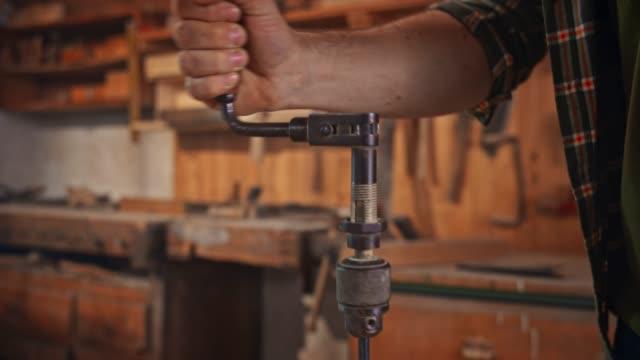 slo mo händerna på en manlig snickare med hjälp av en hand borr för att göra ett hål i träbiten - aktivitet bildbanksvideor och videomaterial från bakom kulisserna