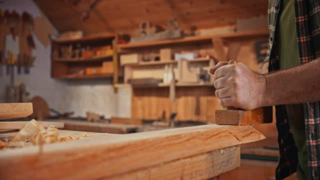 slo mo ahşap bir parça şekillendirmek için bir uçak kullanarak bir erkek marangoz eller - el aleti stok videoları ve detay görüntü çekimi