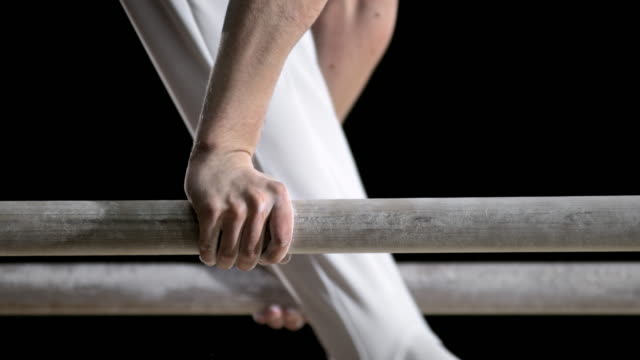 SLO MO Hands of a male gymnast during his routine on parallel bars