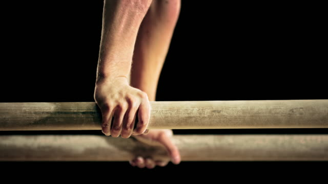 SLO MO Hands of a male gymnast on the parallel bars