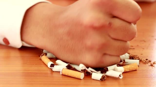 el ile iki yarıya bir sigara kırmak bir adamın elleri. sigara konsepti durdurun. - nikotin stok videoları ve detay görüntü çekimi